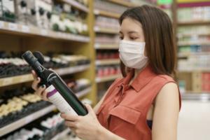 woman choosing wine wearing mask